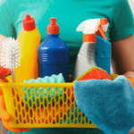 Woman in green shirt gholding basket of cleaning products